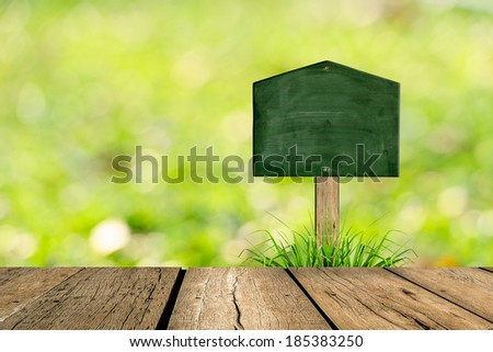 Wooden blackboard sign in grass and bokeh background - stock photo