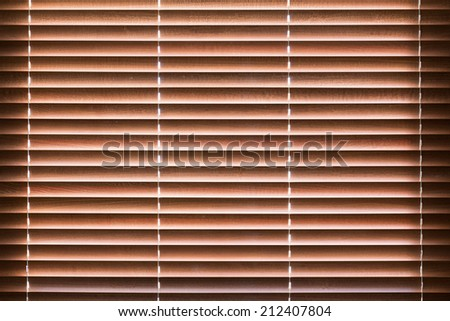 Wooden blinds with daylight illuminating through - stock photo