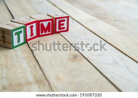 Wooden blocks are Time word on wooden floor - stock photo