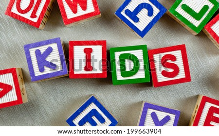 Wooden blocks forming the word KIDS in the center  - stock photo