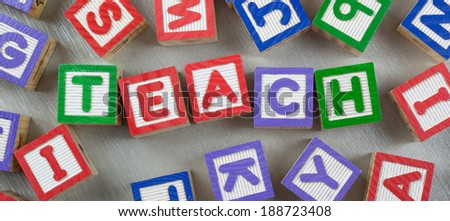 Wooden blocks forming the word TEACH in the center
