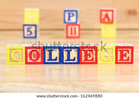 Wooden blocks with letters. Children educational toy concept - future college thinking.