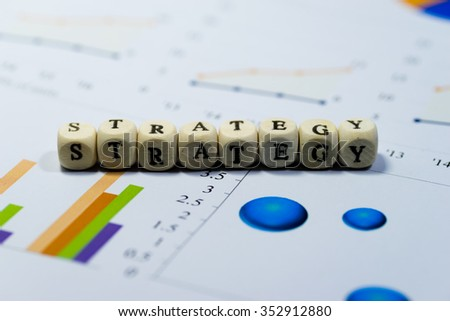 Wooden blocks with the text, STRATEGY, on chart and graph