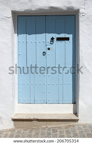 wooden blue door and whitewashed wall  - stock photo