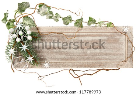 Wooden board decorated with ivy, spruce, stars and artificial berries