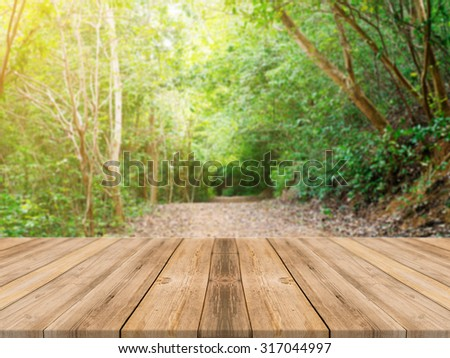 Wooden board empty table in front of blurred background. Perspective brown wood over blur trees in forest - can be used for display or montage your products. spring season. vintage filtered image.