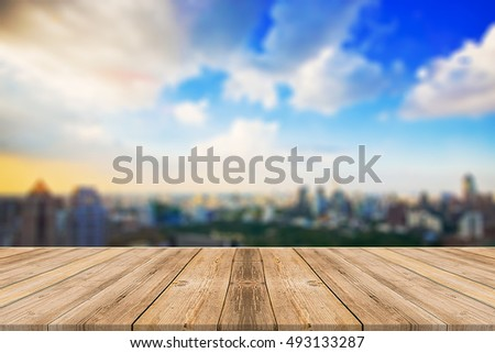 Wooden board empty table in front of blurred background. Perspective sunset city view with twilight sky can be used for display or montage your products.