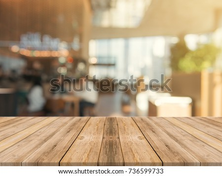 Wooden board empty table top on of blurred background. Perspective brown wood table over blur in coffee shop background - can be used mock up for montage products display or design key visual layout.