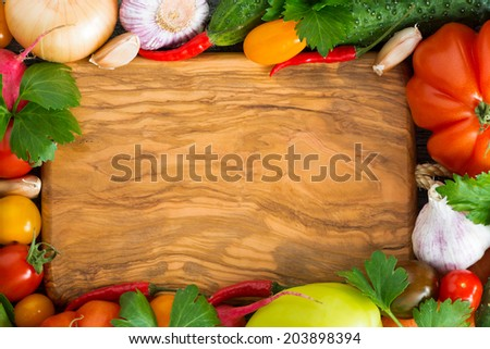 wooden board for recipe, spices and fresh vegetables, top view - stock photo