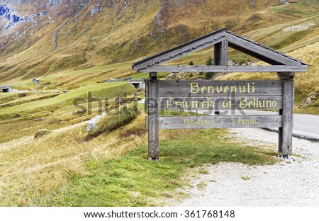Wooden board sign representing :Welcome in Belluno county,Dolomites mountains area,Italy 2015. - stock photo