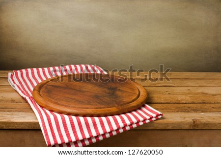 Wooden board stand on tablecloth over grunge background - stock photo