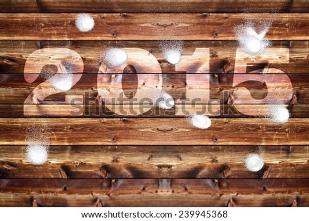 Wooden board with bleached out 2015 letters, which is bombarded with snowballs. - stock photo