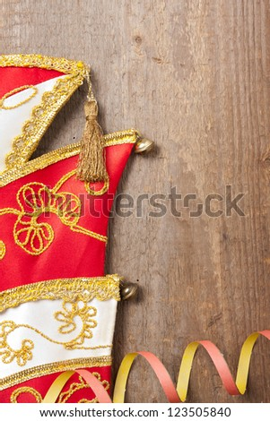 Wooden board with colorful streamers and carnival hat