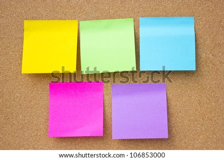 Wooden board with five blank colorful sticky notes. - stock photo