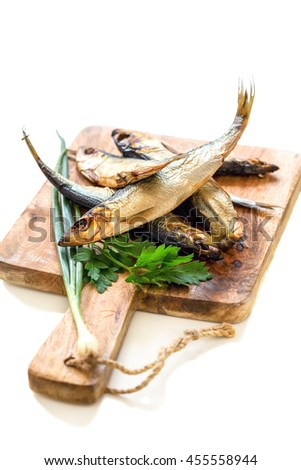 Wooden board with smoked fish, green onions and parsley on a white background. - stock photo