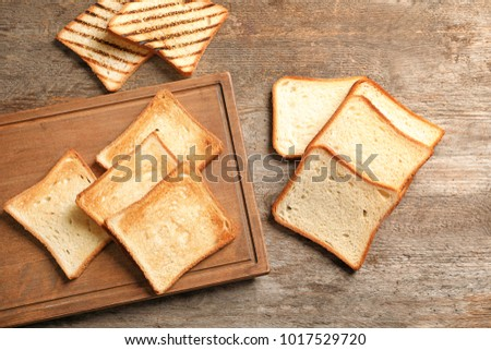 Wooden board with tasty toasted bread on table