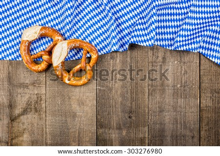 Wooden boards with a bavarian diamond pattern and pretzels - stock photo