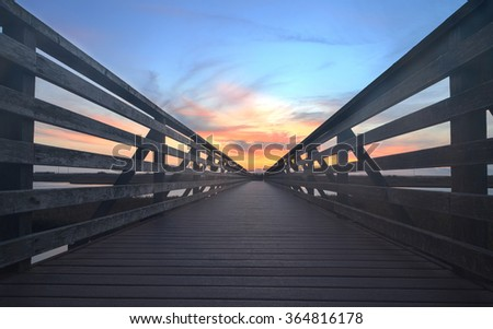 Wooden Boardwalk at sunset, to journey through Bolsa Chica Wetlands preserve in Huntington Beach, California, United States - stock photo