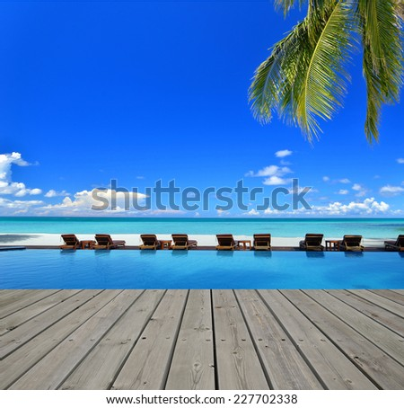 Wooden boardwalk beside tropical resorts blue pool -- Tropical vacations concept - stock photo