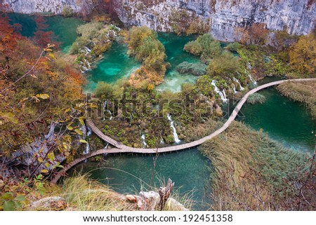 Wooden boardwalk passage in Plitvice National Park. Aerial view. Vivid turquoise lake. - stock photo