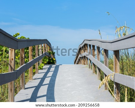 Wooden boardwalk to ocean among sea oats on Sunset Beach at southern tip of Treasure Island Florida on Gulf of Mexico - stock photo