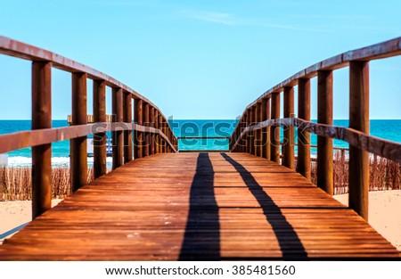 Wooden boardwalk to the beach. Idyllic scene - stock photo