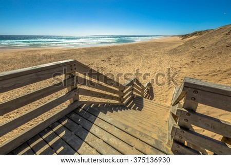 Wooden boardwalks to the beach of Kitty Miller Bay at sunset, in Phillip Island, Victoria, Australia. - stock photo