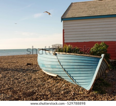 Wooden boat, beach hut, machinery and seagull on beach