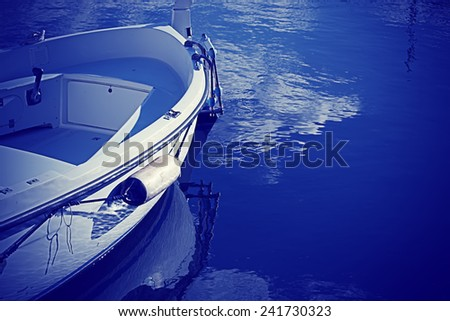 wooden boat by the shore in blue