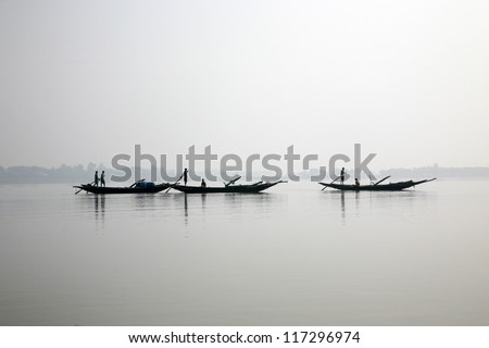 Wooden boat crosses the Ganges River in Gosaba, West Bengal, India. - stock photo