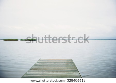 Wooden boat dock in the lake - stock photo