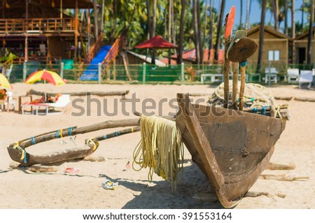 Wooden boat in the sand of tropical beach, Goa, India - stock photo