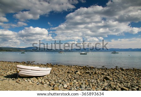 Wooden boat laying on a rocky shore at Lake Tahoe, California on a beautiful day in summer with great big clouds in the sky - stock photo