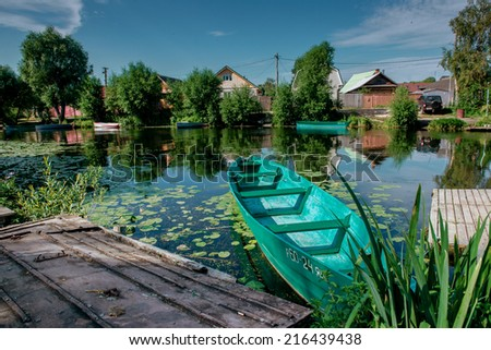 Wooden boat on a river bank near in Russian provincial town Pereslavl-Zalessky. - stock photo