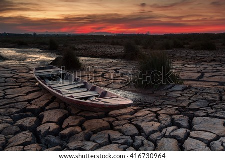 Wooden boat on drought land with red sunset - stock photo