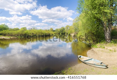 Wooden boat on the river bank - stock photo