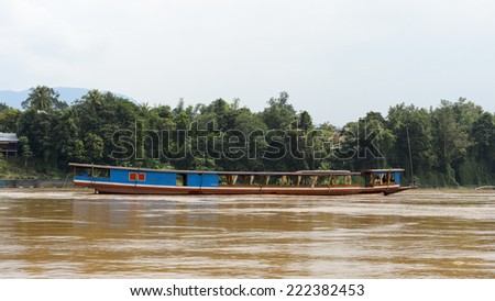 Wooden boat sailing over the Mekong river in Asia