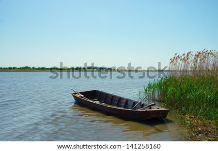 Wooden boat tied up to the bank of the river - stock photo