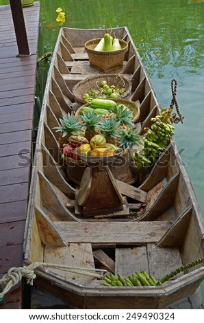 Wooden boat with baskets of fruit at the pier - stock photo