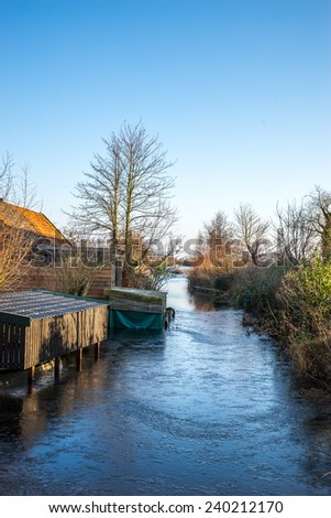 Wooden boathouses along side a frozen canal - stock photo