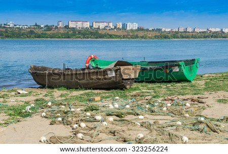 Wooden boats at Danube river bank with Galati cityscape in the background - stock photo