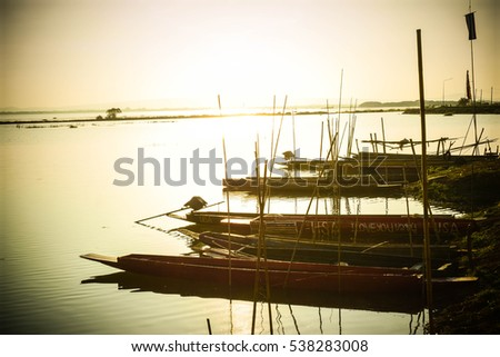 Wooden boats on calm river horizontal and sunset