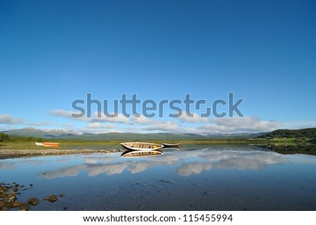 Wooden boats on the mountain lake - stock photo