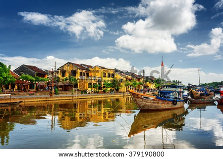 Wooden boats on the Thu Bon River in Hoi An Ancient Town (Hoian), Vietnam. Yellow old houses on waterfront reflected in river. Hoi An is a popular tourist destination of Asia. - stock photo