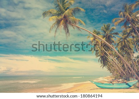 Wooden boats under palm trees on tropical beach, vintage stylized - stock photo