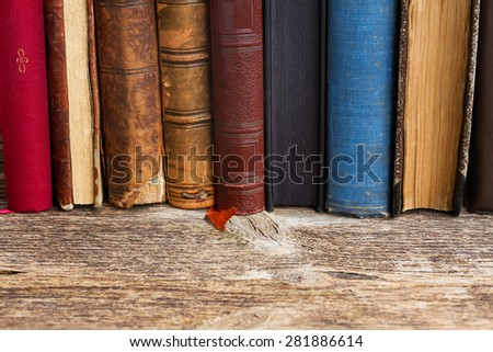 Wooden bookshelf  with row of antique books close up