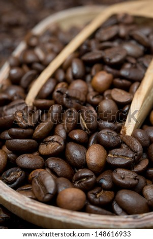 wooden bowl and scoop with coffee beans, selective focus, vertical