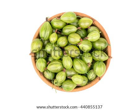 Wooden bowl filled with green gooseberries isolated on a white background, top view