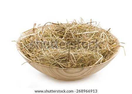 Wooden bowl filled with straw on white