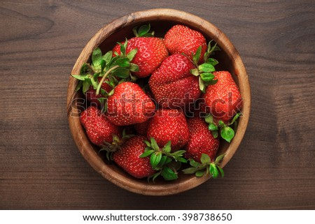 wooden bowl full of fresh strawberries on the brown table - stock photo